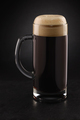 Stein with fresh stout beer with cap of foam on a black. - PhotoDune Item for Sale