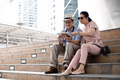 Senior Asian couples sit on stairs, plan, find travel information via tablet. - PhotoDune Item for Sale