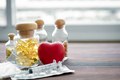 Medicine in glass bottle and heart on wood background. - PhotoDune Item for Sale