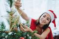 Sexy woman santa decorating Christmas trees. - PhotoDune Item for Sale