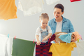 woman and girl hanging clothes on a rope - PhotoDune Item for Sale