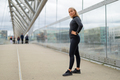 Fit Woman in Black Workout Outfit Standing At Modern Bridge In City - PhotoDune Item for Sale