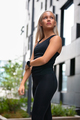 Young Woman in Workout Outfit Standing Against Futuristic Modern Building In City - PhotoDune Item for Sale