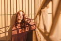 Portrait of young ginger woman against fence - PhotoDune Item for Sale