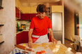 Senior woman cooking cookies in red clothes. - PhotoDune Item for Sale