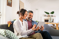 Multiethnic mid adult couple using digital tablet at home - PhotoDune Item for Sale