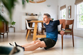 Mature man doing triceps dips using chair at home - PhotoDune Item for Sale
