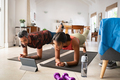 Mixed race couple practicing stretching exercise at home - PhotoDune Item for Sale
