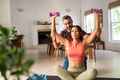 Personal trainer helping woman to do exercise at home - PhotoDune Item for Sale