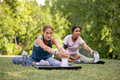 Two women doing stretching exercise at park - PhotoDune Item for Sale