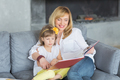 Mother and little daughter are playing, reading a book, sitting and enjoying in a sofa. - PhotoDune Item for Sale