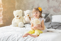 Portrait of child girl having fun sitting and playing with a teddy bears on a bed. - PhotoDune Item for Sale