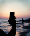 Man takes a sunset photo of girlfriend on the mobile phone - PhotoDune Item for Sale