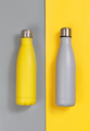 Grey and yellow insulated reusable bottles on grey and yellow background - PhotoDune Item for Sale