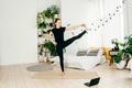 Young woman practicing yoga indoor, watch tutorial. - PhotoDune Item for Sale