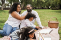 Happy indian family having fun painting with children outdoor at city park - PhotoDune Item for Sale