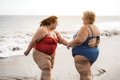 Plus size friends walking on the beach having fun during summer vacation - Focus on right woman back - PhotoDune Item for Sale