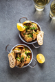 Clams with coriander, lemon and white wine in little pans on gray background, top view - PhotoDune Item for Sale