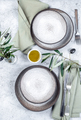 Mediterranean set table. Gray plates, forks, green napkins and olive tree branches - PhotoDune Item for Sale