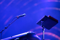 Microphone and music stand in blue stage lights at live concert - PhotoDune Item for Sale