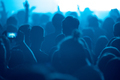 Silhouette of concert crowd at music festival in blue stage lights watching the show - PhotoDune Item for Sale