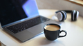 Coffee mug with blurred laptop and headphone on placed on a table in a cafe. - PhotoDune Item for Sale