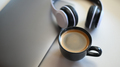 Coffee mug with laptop and headphone on placed on a table in a cafe. - PhotoDune Item for Sale