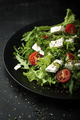 Fresh salad with arugula, cherry tomatoes and feta cheese on a dark background - PhotoDune Item for Sale