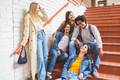Group of friends with ethnic variety, sitting on some street steps having fun together - PhotoDune Item for Sale