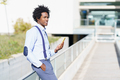 Black man with afro hairstyle using a smartphone near an office building - PhotoDune Item for Sale
