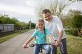 Father teaching her little daughter to ride a bicycle, healthy lifestyle in village at summer day - PhotoDune Item for Sale