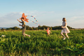 Happy family flying a kite in field. - PhotoDune Item for Sale