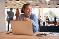 Young Businesswoman With Laptop Sitting At Desk Having Coffee Break In Modern Open Plan Office - PhotoDune Item for Sale
