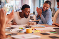 Colleagues Celebrating Businessman's Birthday At Meeting Around Table In Modern Open Plan Office - PhotoDune Item for Sale