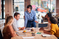 Businessman Giving Presentation To Colleagues Sitting Around Table In Modern Open Plan Office - PhotoDune Item for Sale