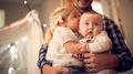 Close Up Of Young Girl Cuddling Baby Brother Whilst Sitting On Father's Knee At Home - PhotoDune Item for Sale