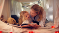 Laughing Mother And Young Daughter Reading Story In Homemade Camp In Child's Bedroom At Home - PhotoDune Item for Sale
