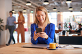 Young Businesswoman Sitting At Desk Using Mobile Phone In Modern Open Plan Office - PhotoDune Item for Sale