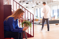 Businesswoman Sitting By Stairs In Modern Open Plan Office Checking Messages On Mobile Phone - PhotoDune Item for Sale