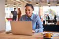 Young Businesswoman Sitting At Desk Working On Laptop In Modern Open Plan Office - PhotoDune Item for Sale