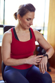 Mature Woman Exercising In Home Gym Checking Health App On Smart Watch - PhotoDune Item for Sale