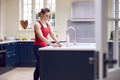 Mature Woman Wearing Fitness Clothing Checking Messages At Home In Kitchen After Exercising - PhotoDune Item for Sale