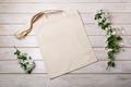 Rustic tote bag mockup with blooming apple tree branch in white vase - PhotoDune Item for Sale