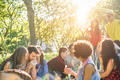 Happy friends eating and drinking red wine at picnic party outdoor - PhotoDune Item for Sale