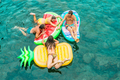 Happy friends floating with lilos mattress inside sea natural pool - PhotoDune Item for Sale