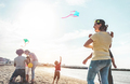 Happy families flying with kite and having fun on the beach - PhotoDune Item for Sale