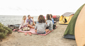 Happy friends having barbecue picnic next to the ocean - PhotoDune Item for Sale