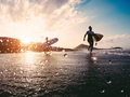 Silhouette of happy surfers running with surf boards on the beach - PhotoDune Item for Sale