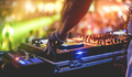 Dj mixing outdoor at beach party festival with crowd of people in background - PhotoDune Item for Sale