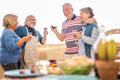 Senior friends having fun drinking wine at barbecue dinner in terrace outdoor - PhotoDune Item for Sale
